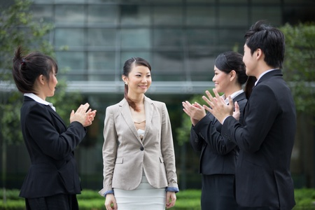 congratulate: Asian business people applauding a colleague. Image depicting success and achievement.