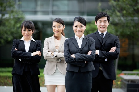 there: Happy Asian business team standing together with there leader.