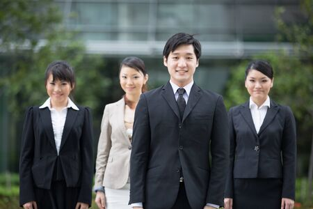 Happy Asian business team standing together with there leader. photo