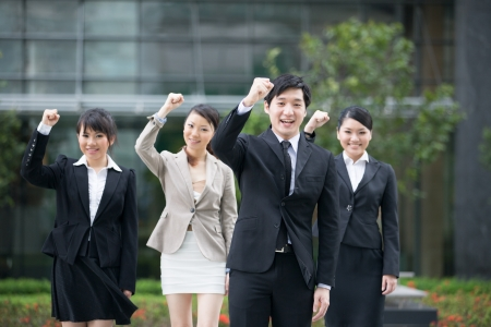 asian executive: Business man celebrating with his team in the background.