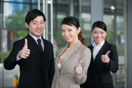 Cheerful Asian business men and women with thumbs up. photo