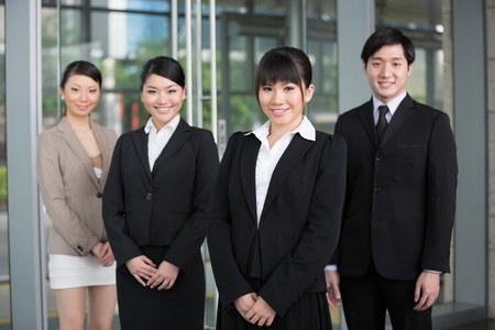 asian business team: Happy Asian business team standing together with there leader.