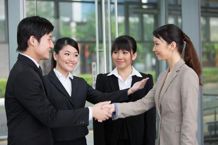 introduced: Hombre de negocios de Asia y la mujer est�n introduciendo y dando la mano. Foto de archivo