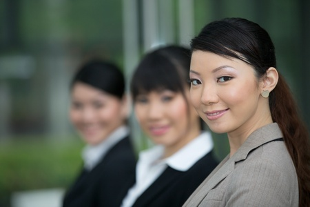 Three happy Asian business women standing in row.  photo