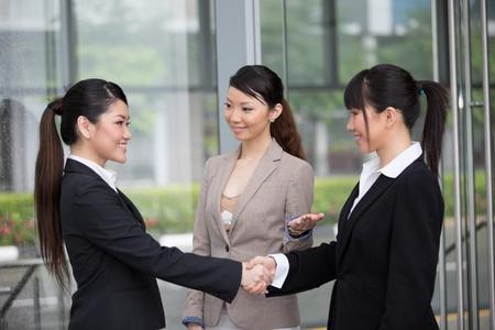 asian business women: Asian business women shaking hands. Stock Photo