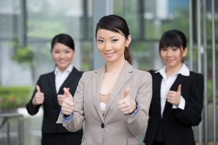 Asian businessman and businesswoman with thumbs up outside office. photo