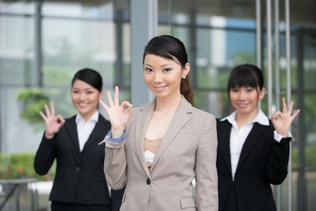 Three happy Asian business woman doing the OK sign.  photo