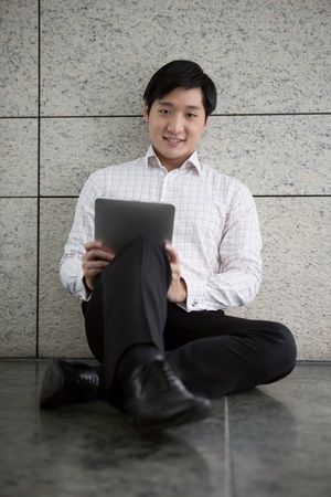 Portrait eines Asian Business Mann mit einem Touch Pad Tablet.