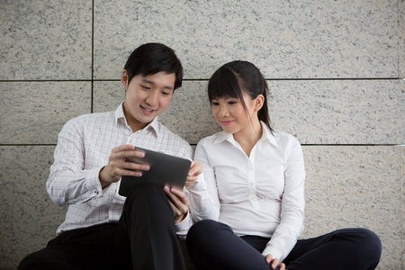 Two business people using a touch pad photo