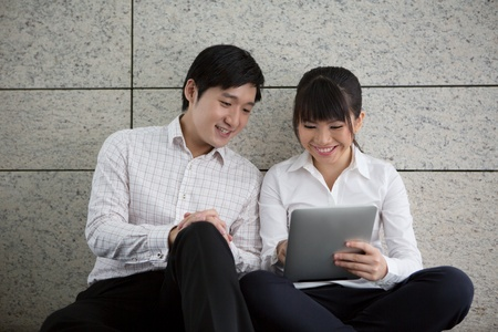 A happy Asian couple using a touch pad photo