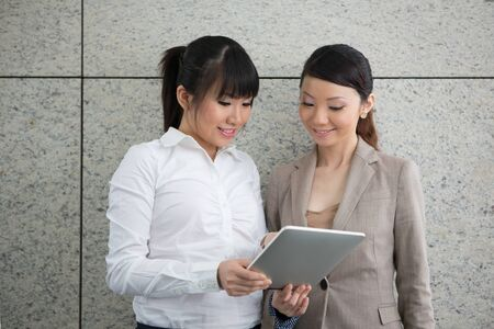 Two Asian women using a digital tablet PC. photo