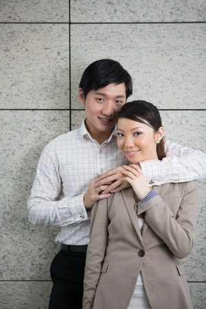 Portrait of a couple leaning against a contemporary wall. photo
