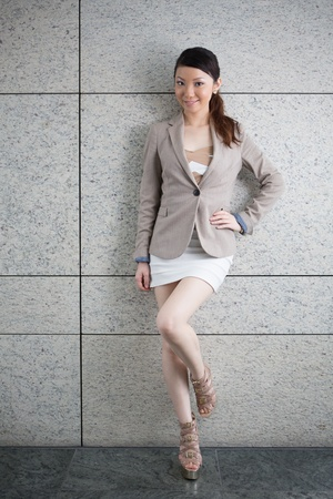 Attractive young Asian woman standing against wall. photo