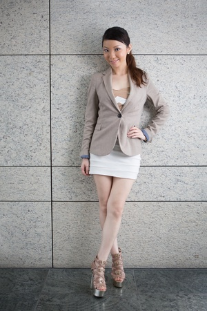 chinese dress: Attractive young Asian woman standing against wall. Stock Photo