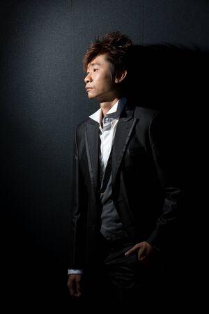 Trendy Asian man posing. Wearing a tuxedo and waistcoat. photo