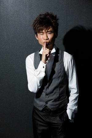 silently: Asian Business man with his finger on his lips asking for silence.