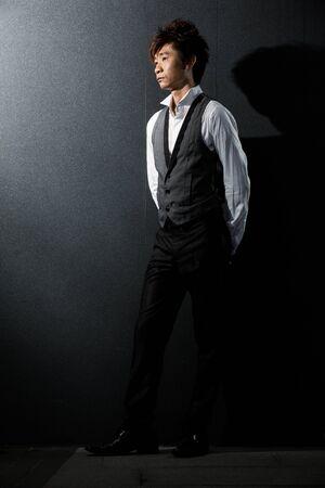 Trendy Asian man posing. Wearing a tuxedo and waistcoat.