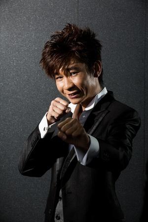 Trendy Asian man throwing a punch. Wearing a tuxedo. photo