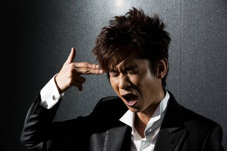 Conceptual portrait of an Asian business man pointing his fingers at his head. photo
