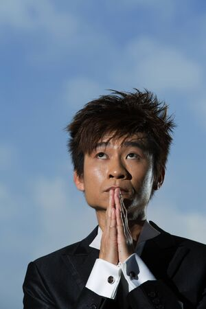 Coneptual image of an Asian Businessman praying for success. photo