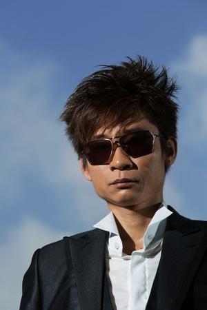 sunglassess: Trendy Asian man posing. Wearing a tuxedo