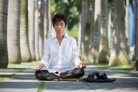 Asian business man meditating in work clothes.  photo
