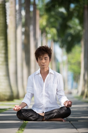 Asian business man meditating in work clothes. Stock Photo - 13184772
