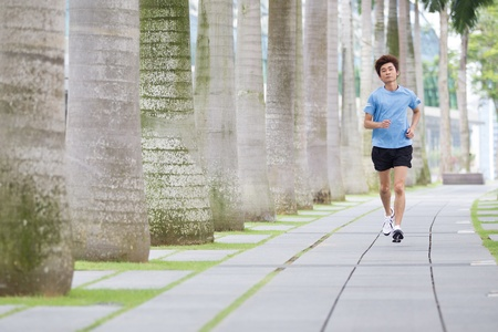 jogging in nature: Asian man running in the park in summer. Stock Photo