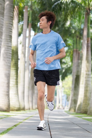 Asian man running in the park in summer. photo
