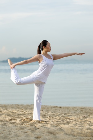Asian woman performing yoga on a beach photo