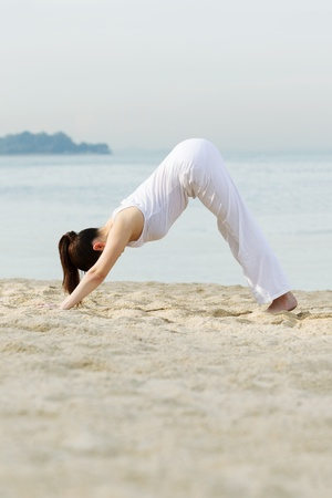 Asian woman performing yoga on beach with sea in background. Stock Photo - 13586837