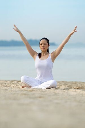 Asian woman performing yoga on a tropical beach photo