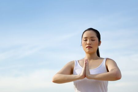 Asian woman performing yoga in front of a blue sky. Stock Photo - 13586838