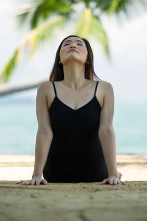 Asian woman performing yoga on beach with sea and palm trees in background photo