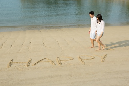 Asian couple in love walking on the beach with the word Happy drawn in the sand. photo