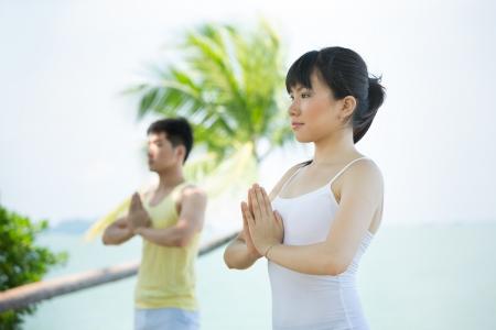 ni�as chinas: Pareja asi�tica que hace yoga en la playa. Foto de archivo