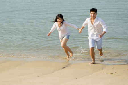 Young Asian couple in love on the beach.  Stock Photo - 13666388