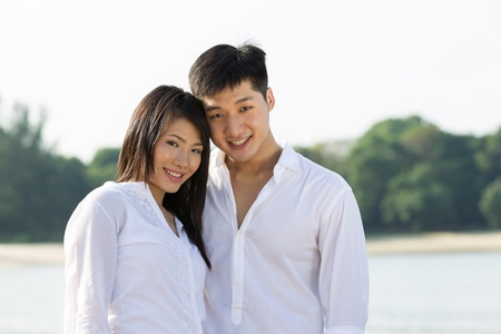 Portrait of a happy Asian couple on the beach. photo