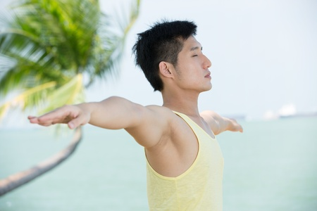 Healthy Asian man doing yoga on a tropical beach. photo