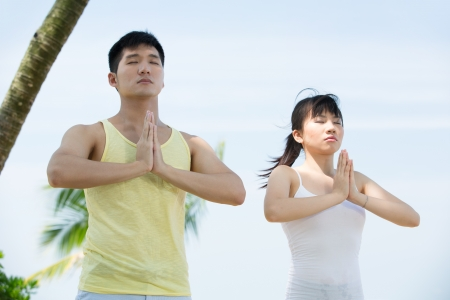 Asian couple doing yoga on the beach. photo