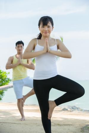 Asian couple doing yoga on the beach. Stock Photo - 13675513