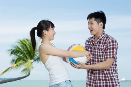 Young couple on a beach vacation having fun with a beachball. photo