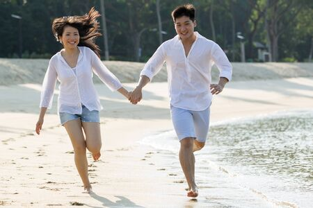 Young Asian couple in love running on the beach.  photo