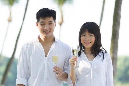 korean fashion: Feliz pareja joven disfrutando de champ�n en una playa tropical.