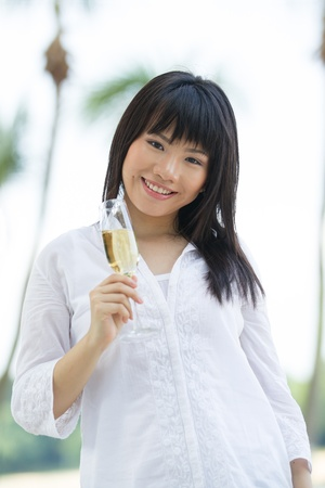 Asian woman drinks champagne on a tropical beach photo