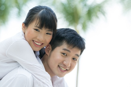 Portrait of a loving Asian couple enjoying themselves on holiday. photo
