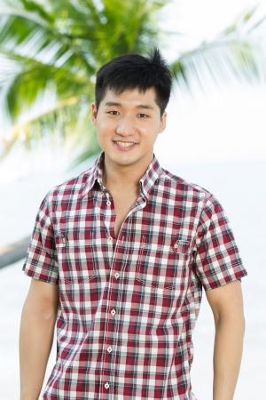 Asian man relaxing on a tropical beach. photo