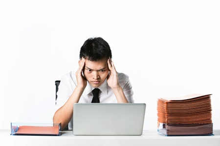 Stressed Asian Business man due to the of amount of work he has to do. photo