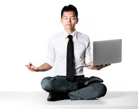 workplace wellness: Asian Business man sitting in lotus position sitting on desk. Stock Photo