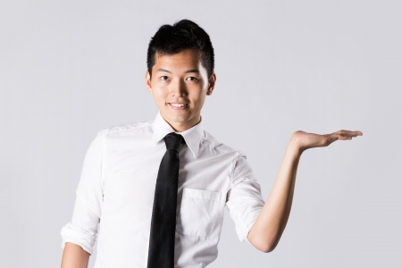 Happy Asian business man holding out his hand with room left for your message. Stock Photo - 13867132